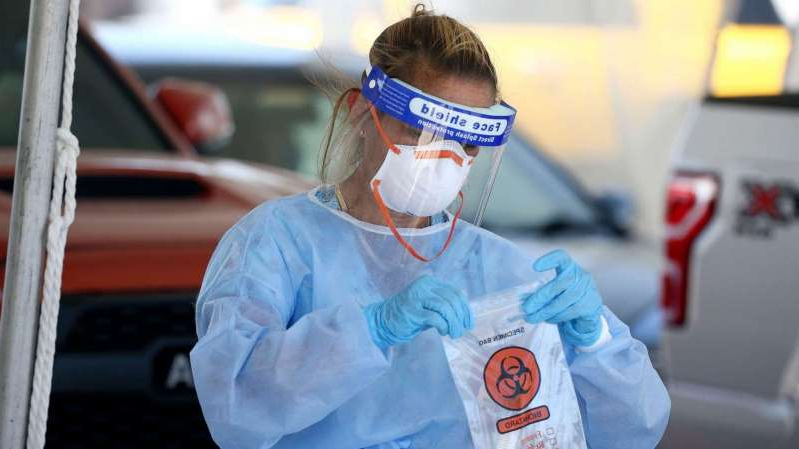 a person wearing a mask: A specimen is secured at a drive-thru coronavirus testing site at South Mountain Community College, July 9, 2020, in Phoenix.