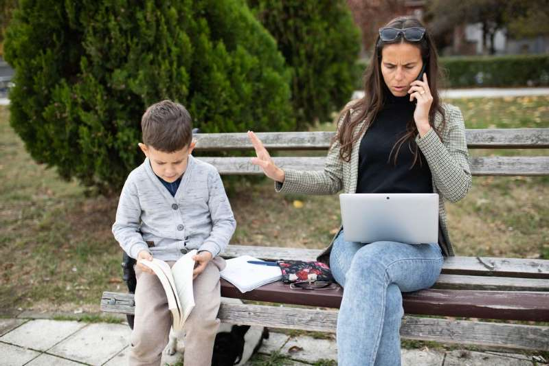 a woman sitting on a park bench: working mom stressed