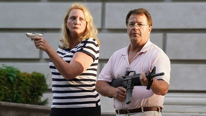 a man and a woman holding a gun: St. Louis couple who pointed guns at protesters have a history of suing neighbors