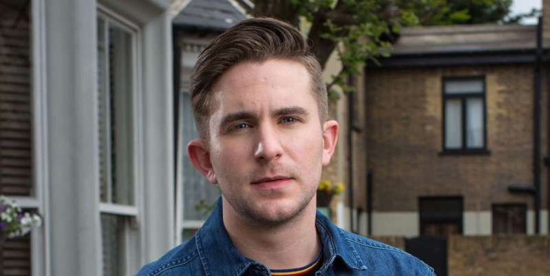 a man wearing a blue shirt standing in front of a building: EastEnders star Tony Clay reveals real-life impact of Callum Highway's sexuality and reveals it was