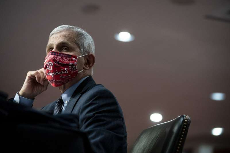 a man wearing a suit and tie: Anthony Fauci, director of the National Institute of Allergy and Infectious Diseases, wears a Washington Nationals protective mask while listening during a Senate Health, Education, Labor and Pensions Committee hearing in Washington, D.C., U.S., on Tuesday, June 30, 2020. The U.S. government's top infectious disease specialist said he's