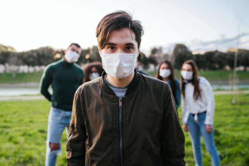 a person standing posing for the camera: Group of teenagers friends at park wearing medical masks.