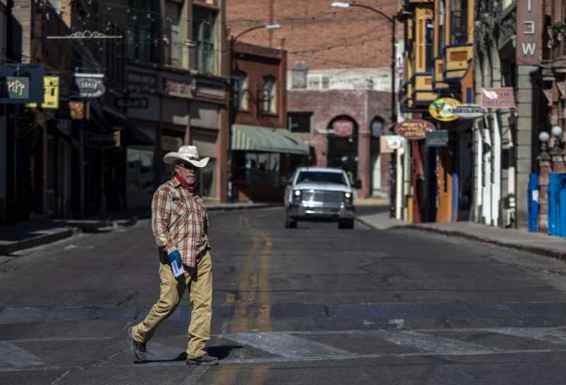 a man walking down a city street: The old mining town of Bisbee, Ariz., was once a haven for anyone searching for a new start. Today, with tourism slowing dramatically, its future is more uncertain. (Brian van der Brug / Los Angeles Times)