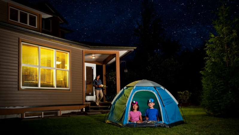 a person standing in front of a building: 12 tips for an epic backyard campout with kids