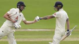 a baseball player holding a bat on a field: England's Ben Stokes, left, fist bumps teammate Dom Sibley to celebrate scoring 150 runs during the second day of the second cricket Test match between England and West Indies at Old Trafford in Manchester, England, Friday, July 17, 2020. (AP Photo/Jon Super, Pool)