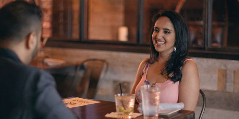 a woman sitting at a table in a restaurant: In this interview, Aparna of Indian Matchmaking gives us an update on her life, her relationship with Jay, and all those memes inspired by the Netflix show.