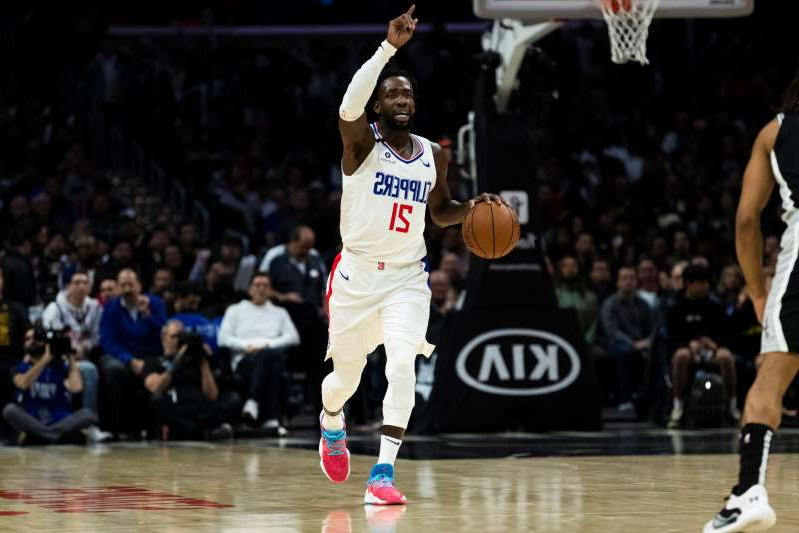 a basketball player jumping up to hit the ball: Patrick Beverley is the latest Clippers player to leave the bubble in Florida. (Ric Tapia/Icon Sportswire/Getty Images)