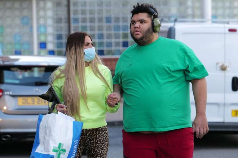 a man and a woman standing in front of a building: Exclusive pictures of Katie Price seen taking her son Harvey home from hospital