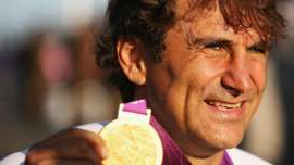a close up of Alex Zanardi smiling for the camera: Alex Zanardi proudly displays the gold medal he won at the 2012 London Paralympics in the Individual H4 Time Trial.
