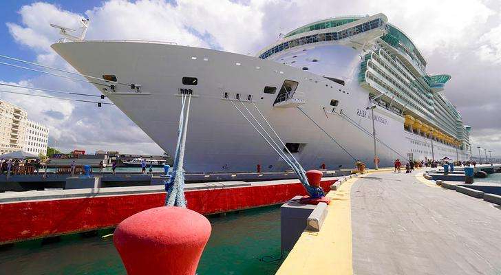 a large ship in the background: Royal Caribbean International's Freedom of the Seas docked in San Juan, Puerto Rico