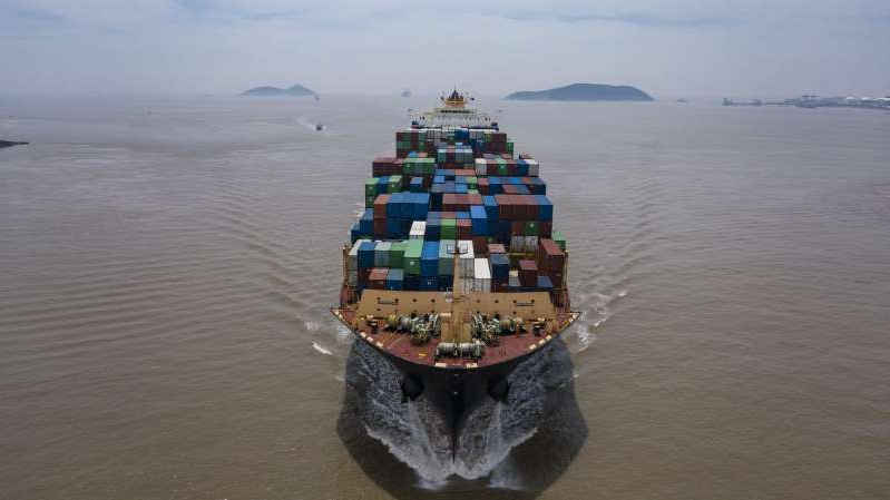 a ship in a body of water: The Kota Cepat vessel loaded with shipping containers approaches the Yangshan Deepwater Port in this aerial photograph taken in Shanghai, China, on Sunday, July 12, 2020. U.S. President Donald Trump said Friday a phase two trade deal with China isn't under consideration, saying the relationship between Washington and Beijing has deteriorated too much.