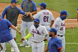 a group of baseball players standing on top of a grass covered field: New York Mets' Yoenis Cespedes, center, celebrates with teammates after a baseball game against the Atlanta Braves at Citi Field, Friday, July 24, 2020, in New York. (AP Photo/Seth Wenig)