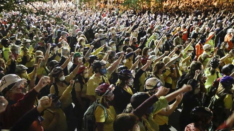 a group of people standing in front of a large crowd of people: William La Jeunesse has an update after another night of unrest in Portland, Oregon.