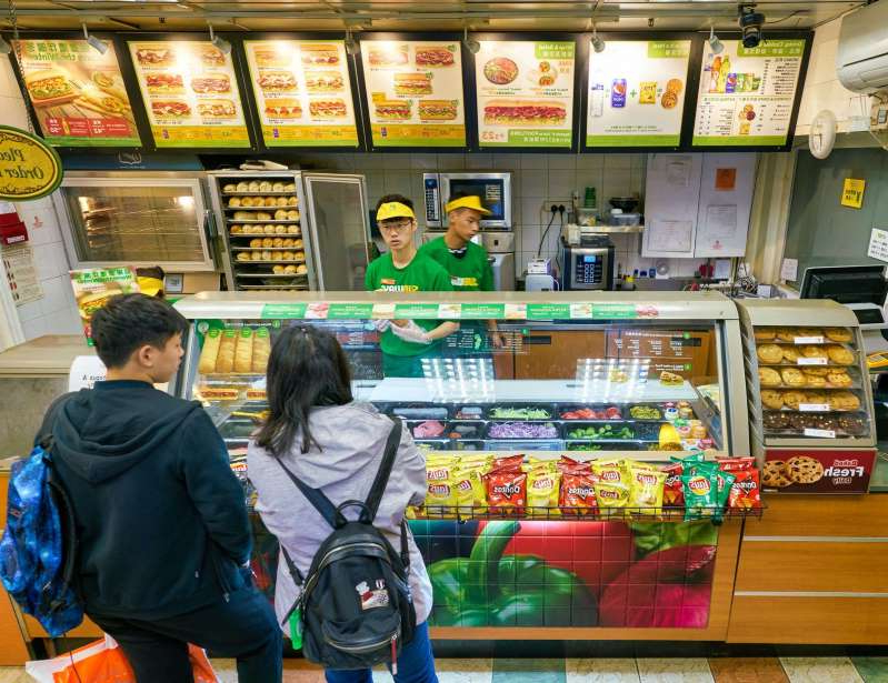 a person standing in front of a store: Subway Menu Items You Won't Find in America