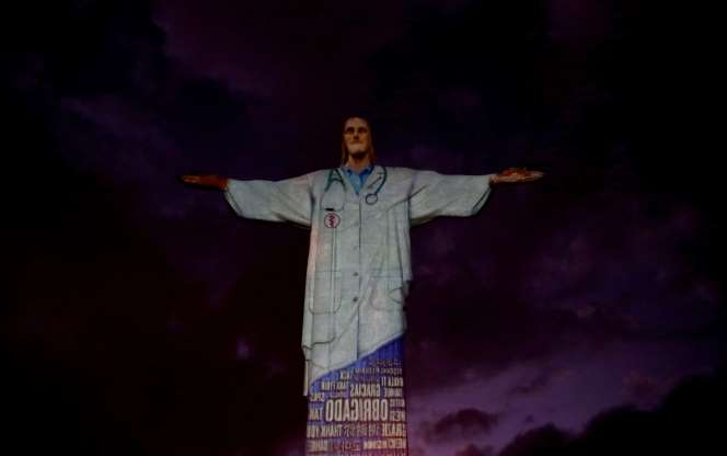 Slide 94 of 110: The statue of Christ the Redeemer is lit up with the image of a medical scrub and the word