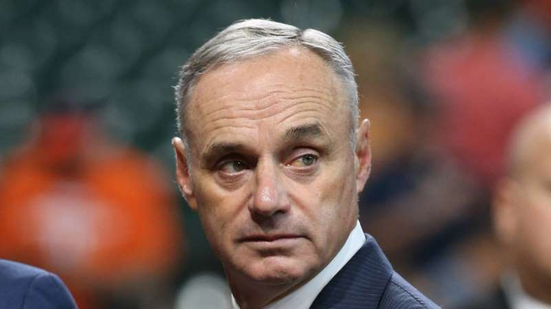 Rob Manfred wearing a suit and tie: MLB commissioner Rob Manfred is taking a positive approach despite a COVID-19 outbreak in his sport.
