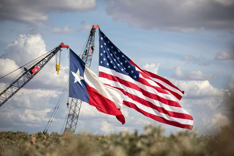 a close up of a flag: MIDLAND, TX - JULY 28: The American and Texas flags are raised at the site of a Double Eagle Energy rig on July 28, 2020 in Midland, Texas. President Donald Trump is making his 16th visit to the state, where he will tour a rig owned by Double Eagle Energy and deliver remarks. (Photo by Montinique Monroe/Getty Images)