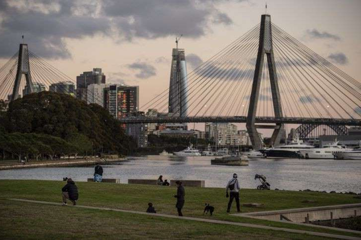 a group of people walking across a bridge over a body of water: GENERIC: ANZAC Bridge, Crown Casino, Blackwattle Bay, Harbour Bridge. 18th June 2020, Photo: Wolter Peeters, The Sydney Morning Herald.