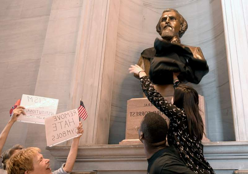 A protester tries to cover the bust of Nathan Bedford Forrest with fabric in Tennessee Capitol in Nashville on Monday, August 14, 2017. In wake of Charlottesville, about 75 protesters took aim at Nathan Bedford Forrest bust which is on display at Tennessee Capitol.