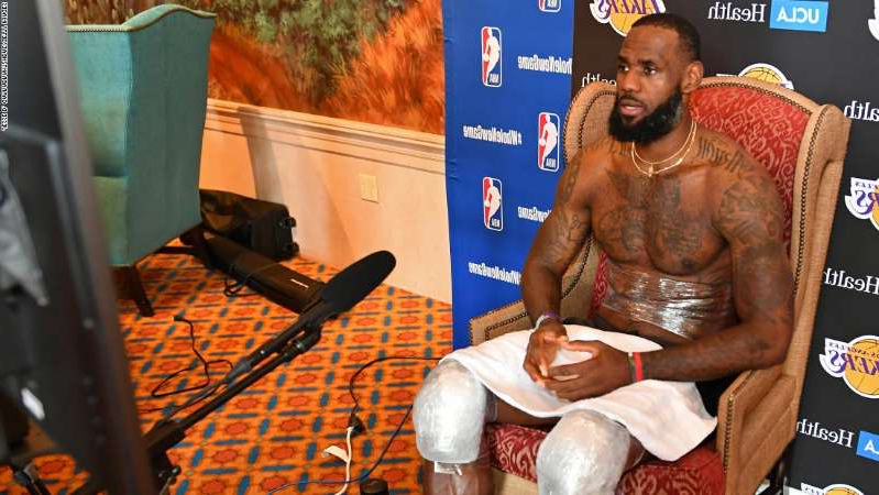 LeBron James sitting on a table: Interviewing NBA stars like LeBron James is very different inside the league's bubble at Walt Disney World, Florida.