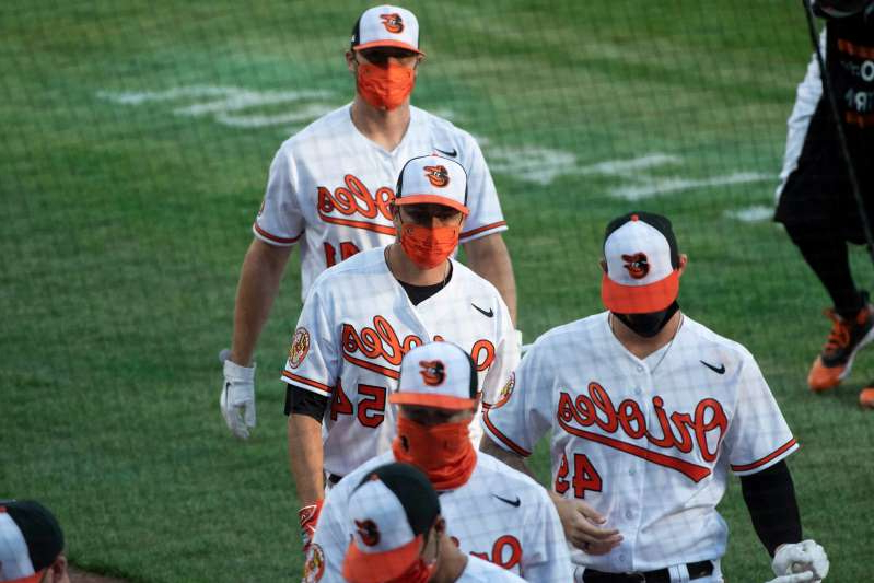 a group of baseball players standing on top of a grass covered field: Orioles players wear masks as they enter the dugout before the game against the Yankees.