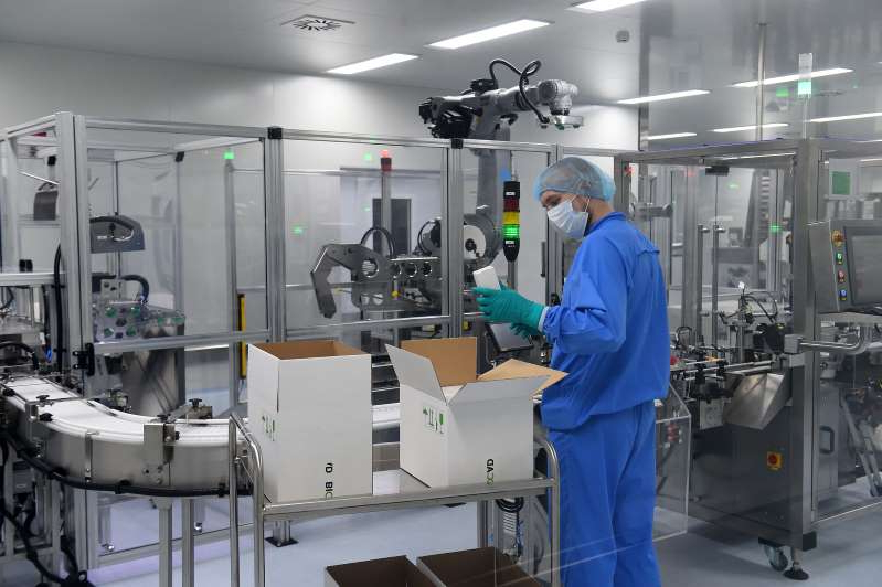 a large machine in a room: A worker is shown at Russia's biotech company BIOCAD which is developing a COVID-19 vaccine at its research centre in Siberia, Vektor. A vaccine at Moscow's Gamaleya Institute is expected to be rolled out in October, the country's health minister has said.