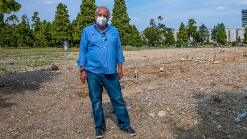 a man standing on top of a dirt field: Vando spent weeks searching for his brother, only to find him at this Milan graveyard for COVID-19 victims. (ABC News: Davide Preti)