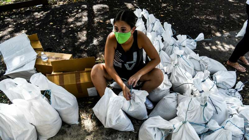 a person sitting on a bench: A woman prepares sand bags for distribution to the residents of Palmetto Bay near Miami