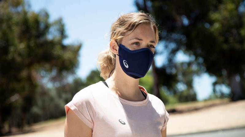 a person talking on a cell phone: ASICS face mask ASICS Runners Face Cover