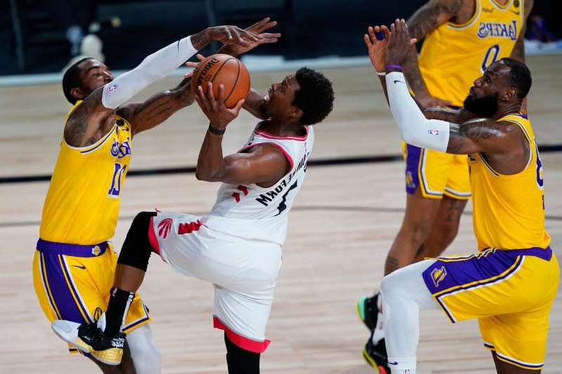 a group of people on a court: Kyle Lowry drives to the bucket against J.R. Smith.