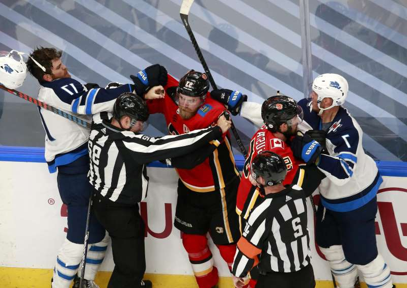a group of people that are standing in the snow: Aug. 1: The Winnipeg Jets and Calgary Flames get in a scrum after the final whistle of Game 1.