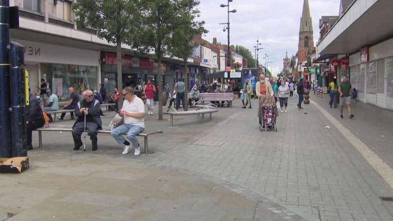 a group of people walking on a sidewalk: Traders in the West Midlands fear another lockdown
