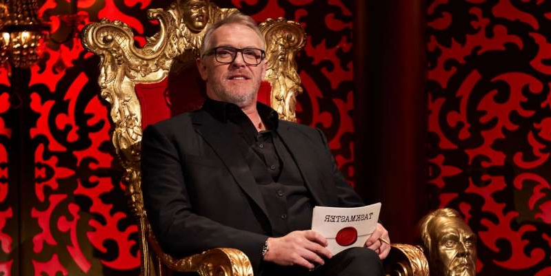 Greg Davies sitting at a table with wine glasses: Taskmaster presenters Greg Davies and Alex Horne discuss how comedy challenge show will look on Channel 4 for Series 10 after BAFTA win.
