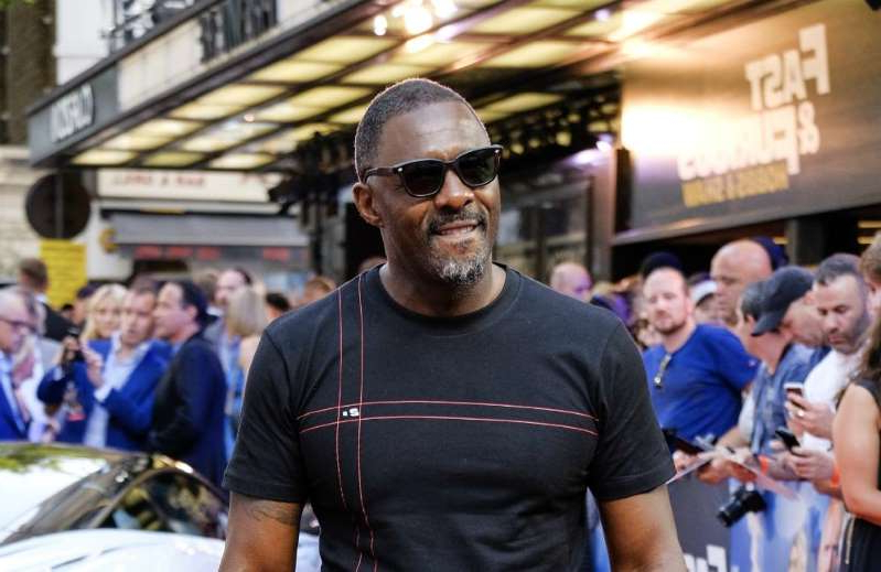 Idris Elba standing in front of a building