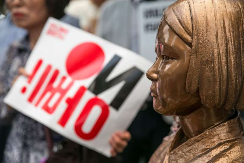 a man holding a sign: An attendee, right, holds a placard reading 'No Abe!' next to the statue of a girl representing a 'comfort woman' in world war two during a demonstration against Japan's removal of South Korea from a list of trusted trading partners in Seoul, South Korea, on Saturday, Aug. 3, 2019. South Korea warned Japan it would be responsible for repercussions from its unprecedented decision, as escalating tensions between the two U.S. allies threaten to damage security ties and global supply lines.
