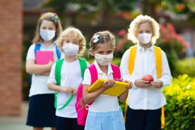 a group of people wearing costumes: School child wearing face mask during corona virus and flu outbreak. Boy and girl going back to school after covid-19 quarantine and lockdown. Group of kids in masks for coronavirus prevention.