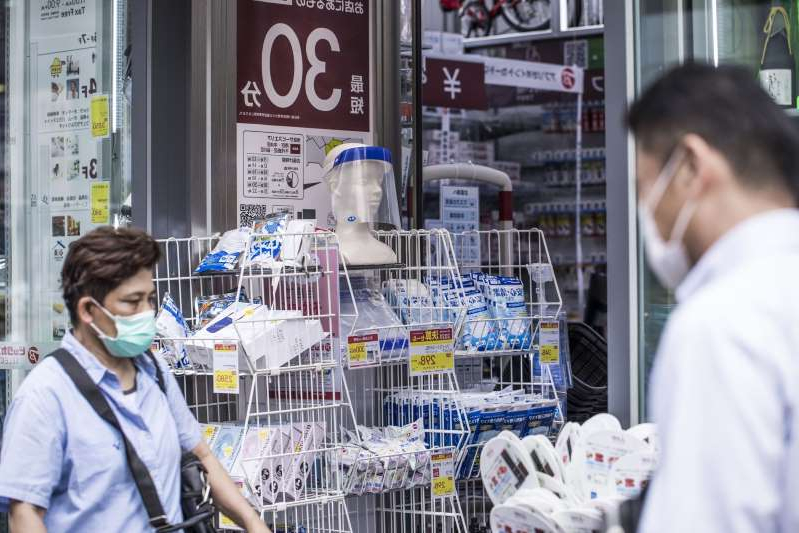 a man and a woman standing in front of a store: A face shield and other sanitizing products are displayed for sale at a drug store in the Roppongi district of Tokyo, Japan, on Thursday, July 30, 2020. Officials in Japan are planning stricter measures on businesses and group activities as coronavirus cases continue to spread from a concentration around the capital to other urban areas across the country.