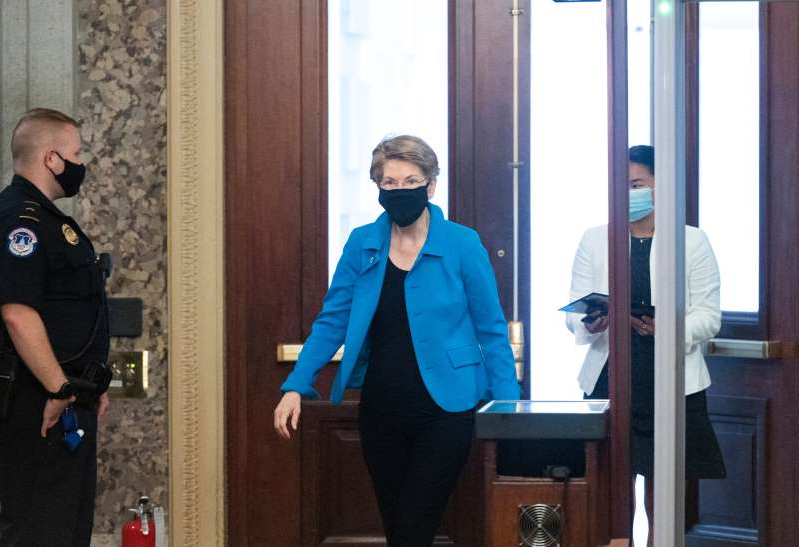 a man and a woman standing in front of a window: Sen. Elizabeth Warren, D-Mass., is questioning the timing of some Kodak stock transactions.