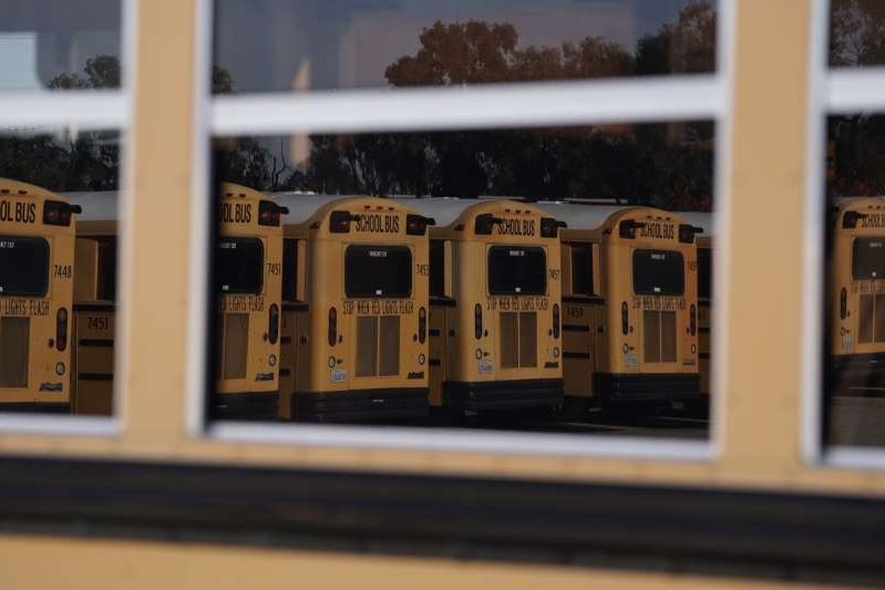 a close up of a store: Navistar International Corp. school buses are seen reflected in the window of a bus stored at the San Diego Unified School District Transportation Department in San Diego, California, U.S., on Thursday, July 9, 2020. The U.S. economy is caught in the middle of President Trump's tug-of-war to reopen schools -- and could end up damned no matter what happens.