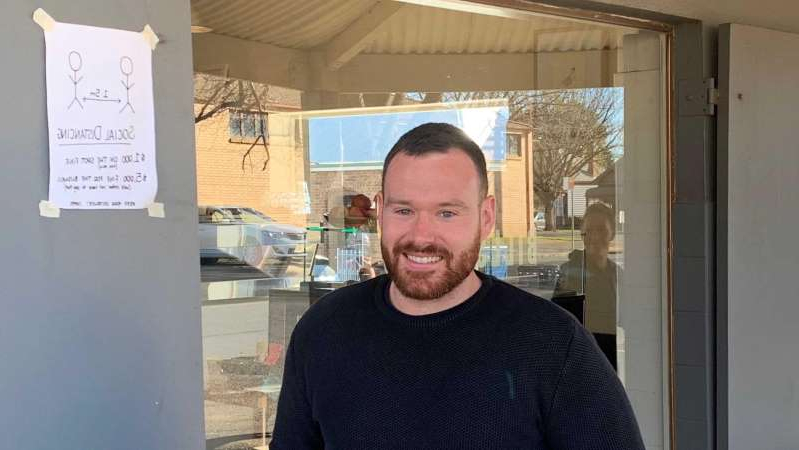 a man standing in front of a window: Orange cafe owner, Ricky Carver, is frustrated that some tourists are not following COVID-19 rules when visiting regional NSW. (By Joanna Woodburn)