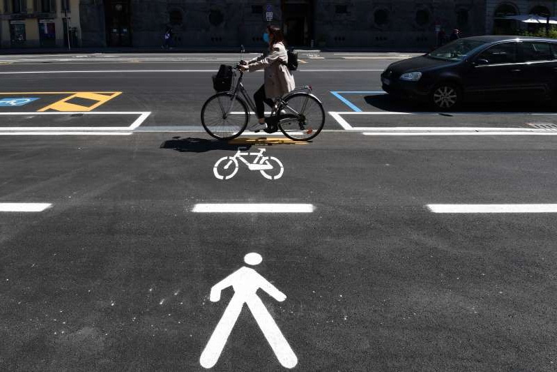 a person riding a bicycle on a city street: A woman rides a bicycle through a bike lane in central Milan on May 4, 2020,
