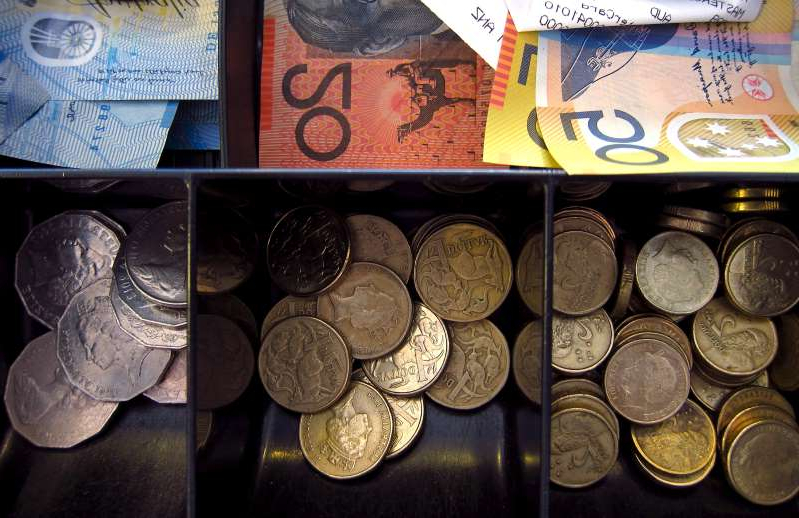 Australian dollar notes and coins can be seen in a cash register at a store in Sydney