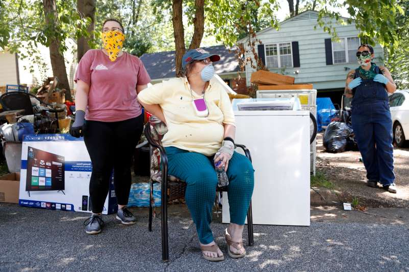 a group of people posing for the camera: Leslie Nelson's sits in front of her belongings outside her Raleigh home after being served with eviction papers on Thursday, April 6, 2020, in Memphis, Tenn.