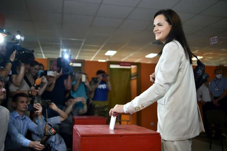 a man and a woman standing in a room: Presidential candidate Svetlana Tikhanovskaya casts her ballot in Minsk
