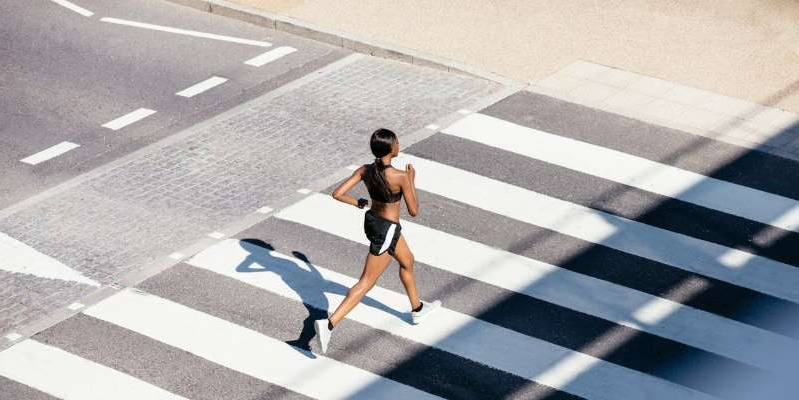 a person crossing the street in front of a crosswalk: Coaches share instant strategies to help you bring the joy back to your miles.