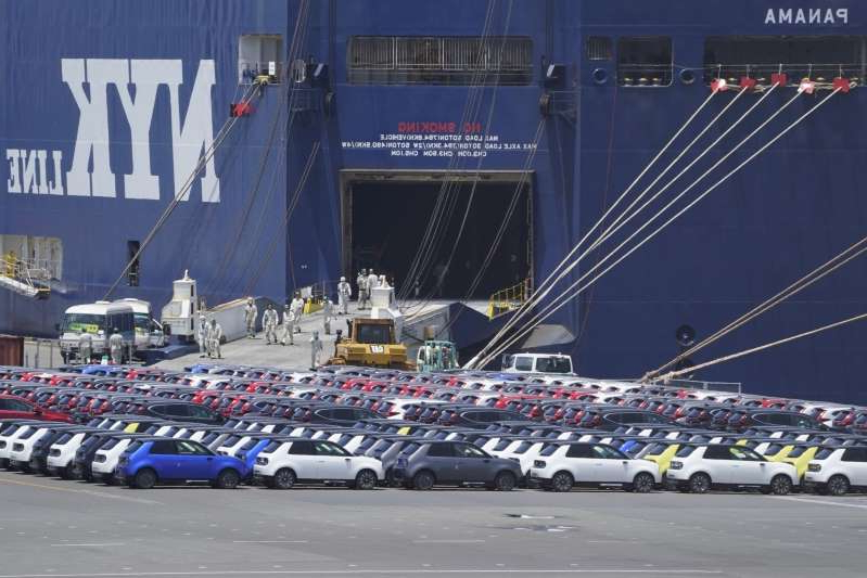 a row of parked cars: Honda Motor Co. vehicles bound for shipment sit at a yard in front of the Nippon Yusen K.K.'s Oceanus Leader vehicle carrier ship at a port in Yokohama, Japan, on Sunday, July 19, 2020. Japanese exports fell by more than 20% for a third straight month even as key markets started to reopen from virus shutdowns.