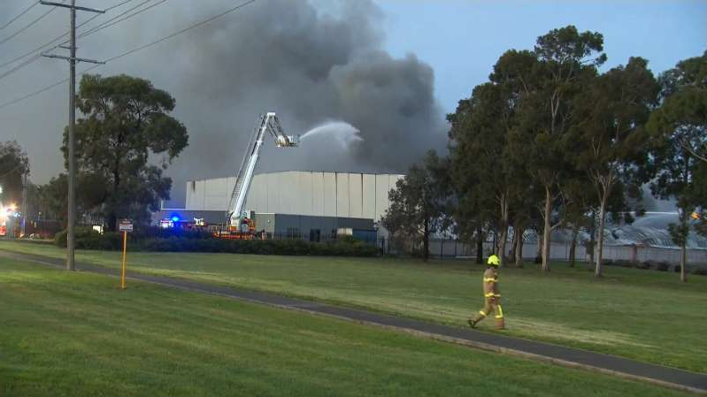 a train on a track with smoke coming out of it: The roof on one side of the 90m x 50m warehouse is threatening to collapse.