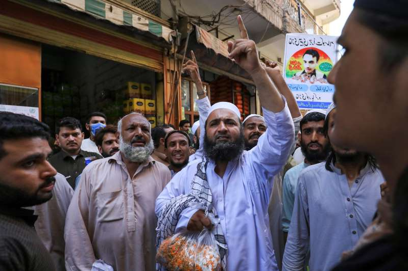 a group of people standing in front of a building: People chant slogans in favour of a man who, according to the Pakistani police, is suspected of killing U.S. national Tahir Ahmed Naseem during a proceeding at a judicial complex, in a protest rally demanding his release, in Peshawar,