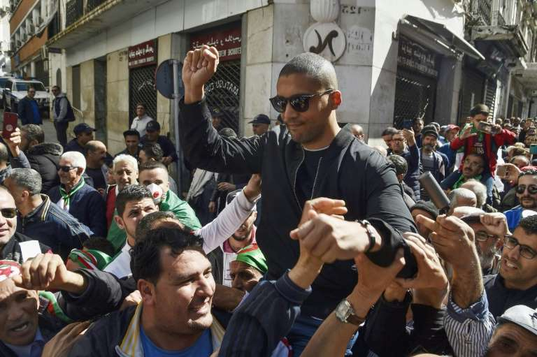 a group of people standing in front of a crowd: Algerian journalist Khaled Drareni, 40, was arrested on March 29 on charges of 'inciting an unarmed gathering' and 'endangering national unity' after covering demonstrations by anti-government protesters