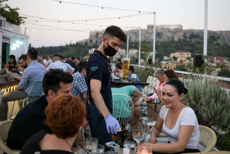 a group of people sitting at a table: A waiter serves patrons at a bar in Athens, Greece on August 1. Since the country began lifting lockdown restrictions, the number of coronavirus cases has spiked.
